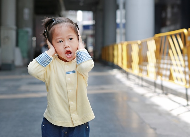 Cute little child girl shutting down her ears, holding her hands covers ears not to hear.