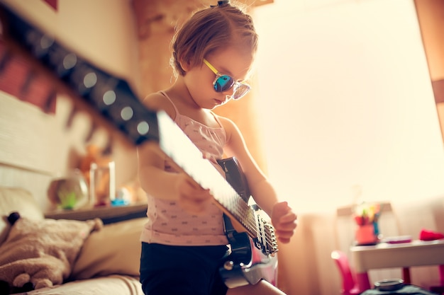 Cute little child girl in sunglasses playing guitar.