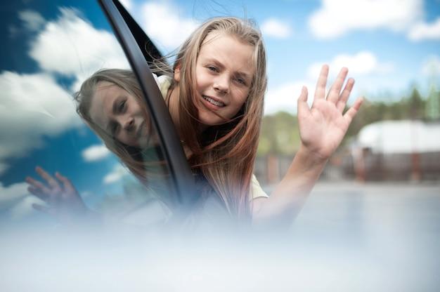 귀여운 어린 소녀 십대는 웃고 차를 타고 여행하며 도시의 차창에서 밖을 내다보며 즐거운 시간을 보냅니다.
