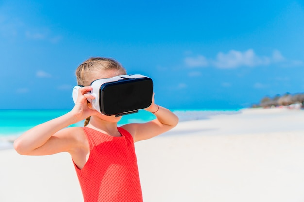 Cute little child girl using vr virtual reality goggles. adorable girl look into the virtual glasses on white beach