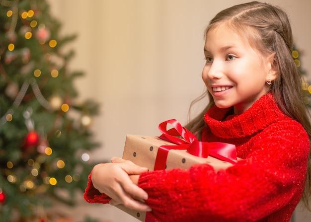 Милая маленькая девочка ребенка с настоящей подарочной коробкой возле елки дома.