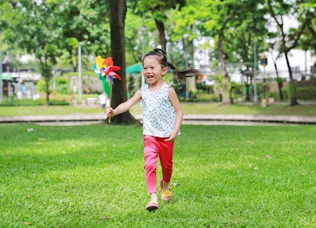 ガーデンに風車を持つかわいい小さな子供の女の子