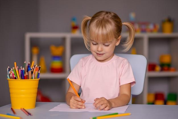 Милая маленькая девочка, писать карандашами в детском саду