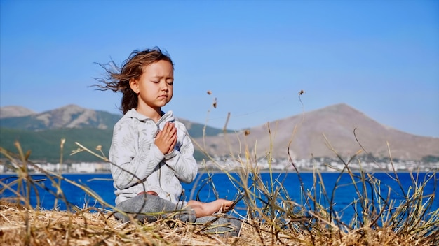Cute little child gurl meditating alone in lotus pose at lake shore