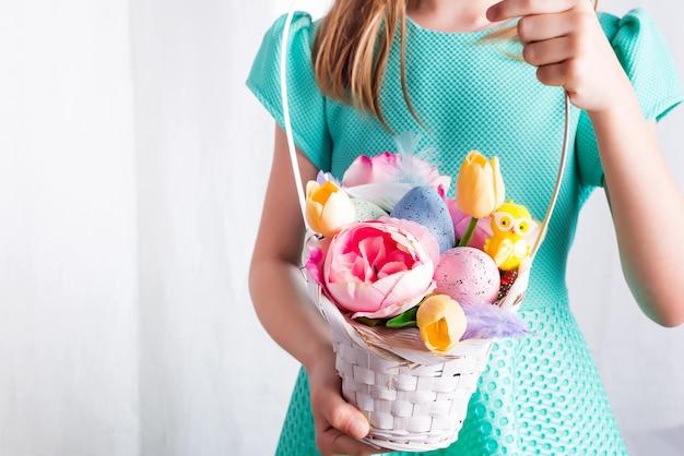 Милый маленький ребенок, холдинг корзина с крашеные яйца и цветы на день пасхи.