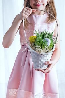 Милый маленький ребенок, холдинг корзина с крашеными яйцами на день пасхи.