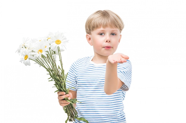 Cute little child holding flowers. boy with camomile. adorable kid congrats his mom with flower bouquet. isolated boy on white background.