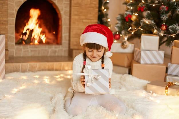 크리스마스 선물 상자 벽난로와 크리스마스 트리 근처 부드러운 카펫에 바닥에 앉아있는 동안 집에서 포즈와 붉은 축제 모자에 귀여운 작은 아이. 땋은 매력적인 소녀는 선물 상자를 보유하고 있습니다.