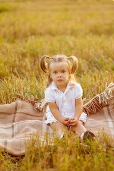 緑のフィールドでポーズをとって白いドレスを着たかわいい小さな子供と