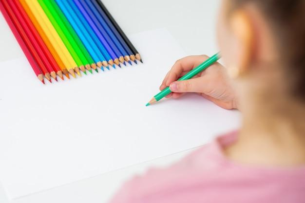 Милый маленький ребенок рисует цветными карандашами на белой бумаге. скопируйте место для текста. макет. выборочный фокус.