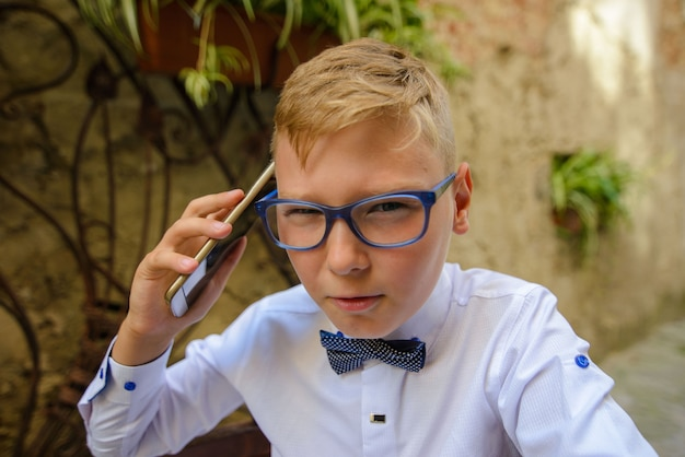 Cute little child is talking on his smartphone while standing in his business suit near a concrete wall. mock up