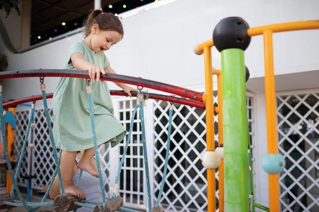 Милый маленький ребенок платит на детской площадке