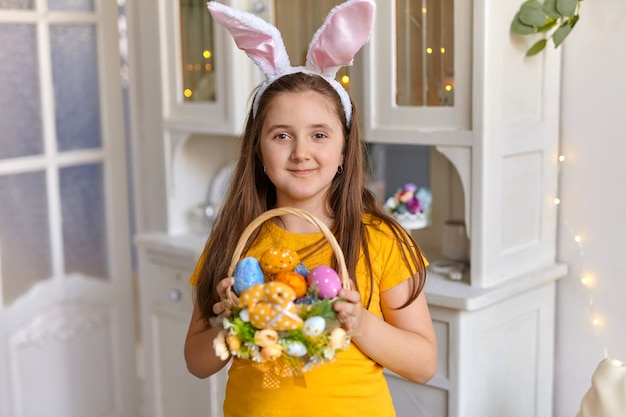 Cute little child wearing bunny ears on easter day. girl holding basket with painted eggs in sunny spring day indoor.