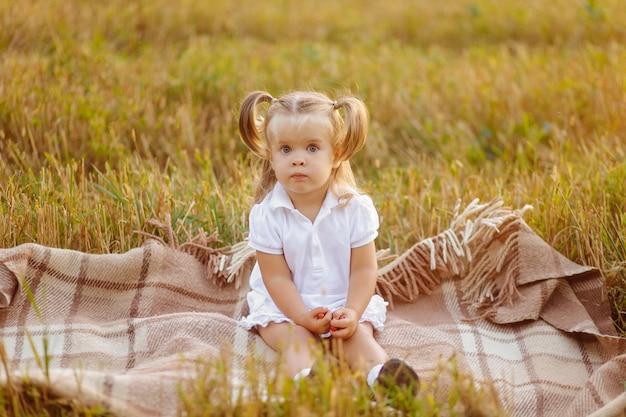 Piccolo bambino sveglio in vestito bianco che posa sul campo verde e