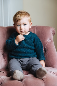 Cute little child with plump cheeks, blonde hair, wears fashionable clothes, sits on armchair