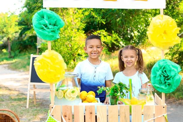 Симпатичные маленькие дети на лимонадной стойке в парке