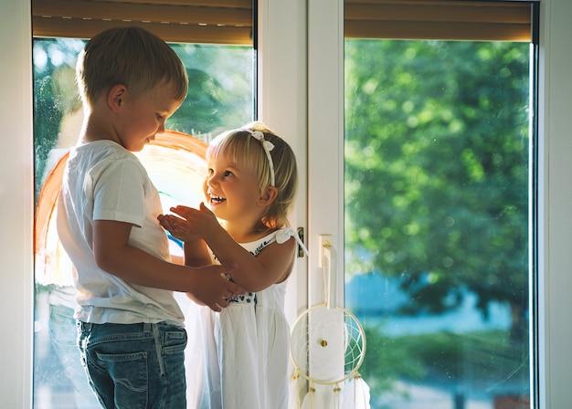 Cute little children on background of painting rainbow on window