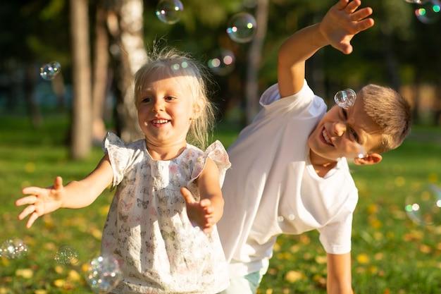 화창한 날 가을 공원에서 귀여운 어린 소년과 소녀가 거품을 불고 있습니다.