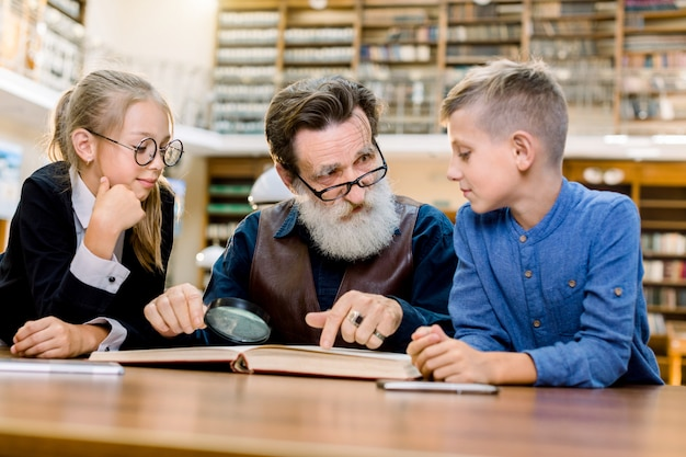 Cute little children, boy and girl reading book with their grandfather at city library
