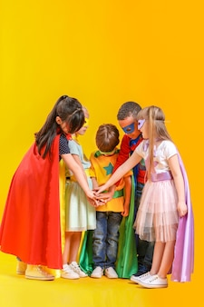 Cute little children dressed as superheroes on color