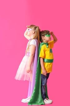 컬러 배경에 슈퍼히어로 옷을 입은 귀여운 아이들