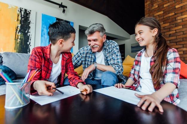 Simpatici bambini che dipingono al tavolo di legno con il loro insegnante nella sala giochi.