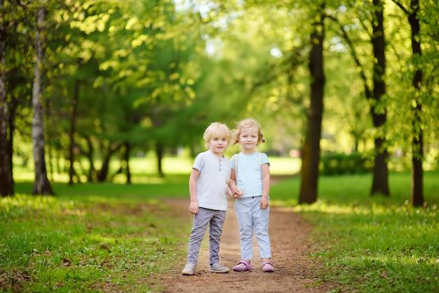 一緒に遊んで、日当たりの良い夏の公園で手を繋いでいるかわいい子供たち