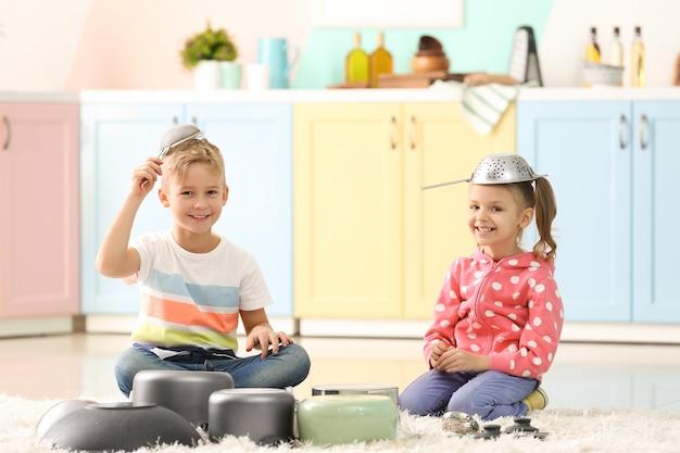 집에서 주방 용품을 가지고 노는 귀여운 어린 아이