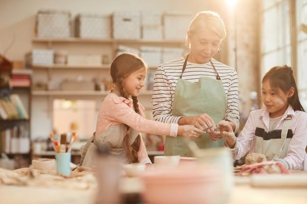 Cute little children in pottery workshop