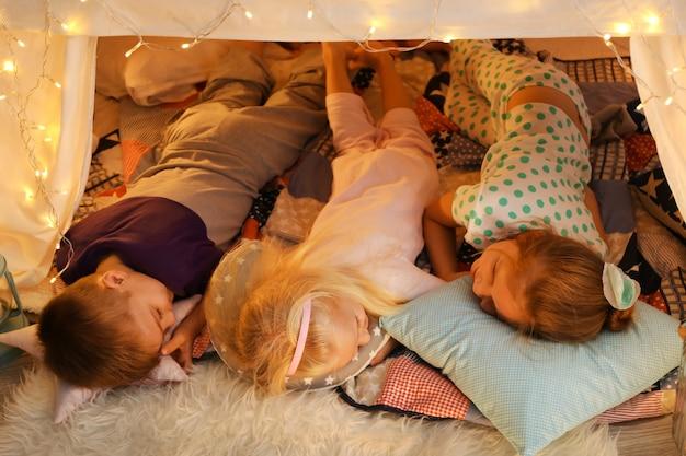 집에서 오두막집에서 자고 있는 귀여운 아이들