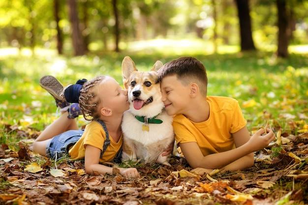 Милые маленькие дети с собакой в парке