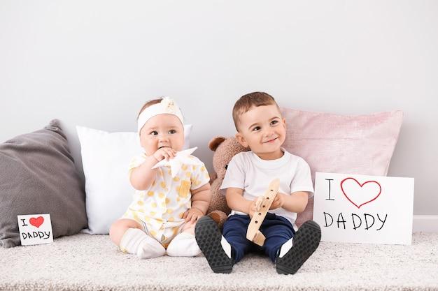 Милые маленькие дети с поздравительной открыткой на день отца у светлой стены