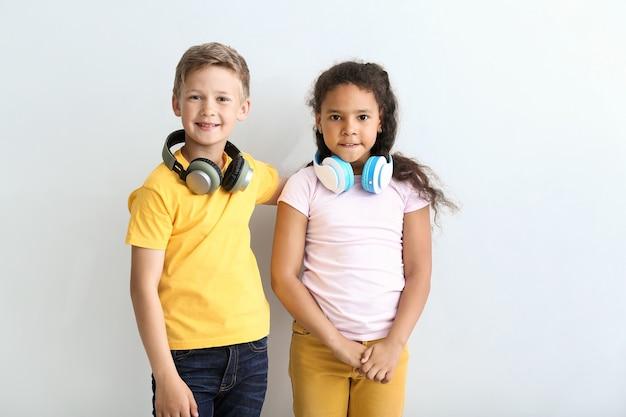Симпатичные маленькие дети с наушниками на светлой поверхности