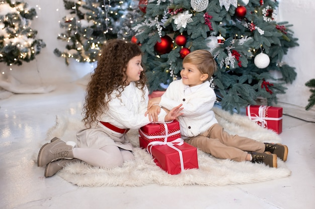 Cute little children with presents in their hands near christmas tree and lights on background. merry christmas and happy holidays.