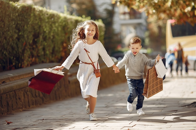 Cute little children with shopping bag in a city