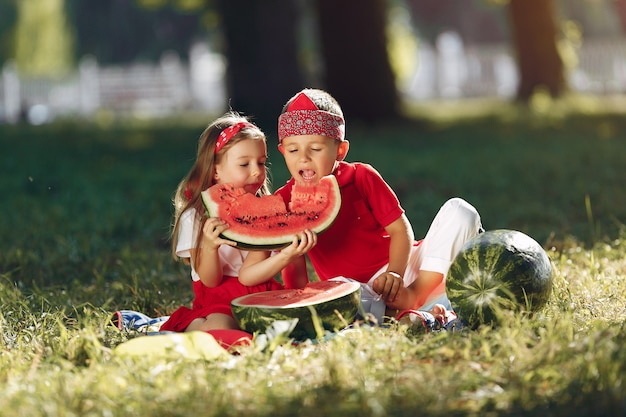 Cute little children with watermelons in a park