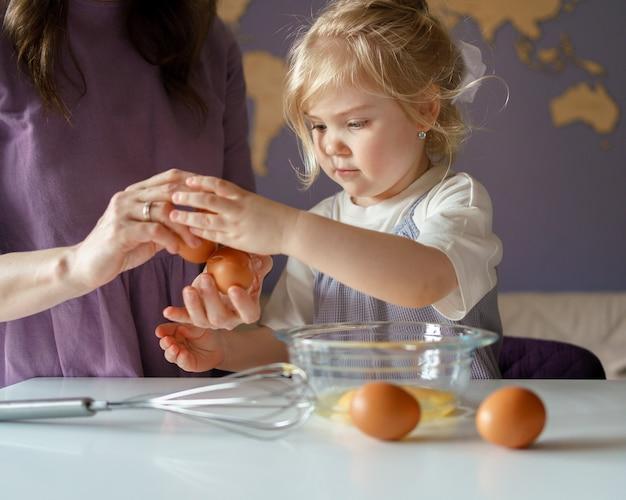 Милый маленький ребенок помогает маме готовить, девочка разбивает яйца в миску