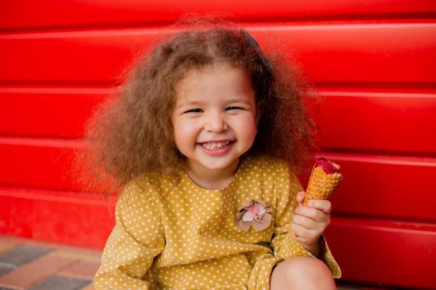 かわいい巻き毛の女の子が笑い、赤いフェンスの近くのアイスクリームを食べる