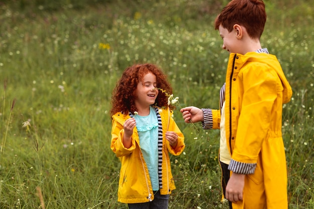 Cute little curly haired ginger girl smelling flowers while standing with older brother dressed in similar yellow raincoat on green meadow in summer day