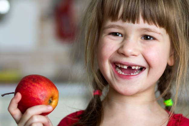 A cute little curly toothless girl smiles and holds a red apple.