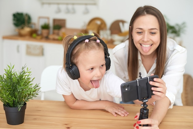 Cute little daughter is sitting next to mom in the kitchen laughing having fun using a smartphone