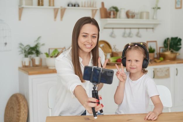 かわいい小さな娘がスマートフォンを使って楽しんで笑ってキッチンでお母さんの隣に座っています