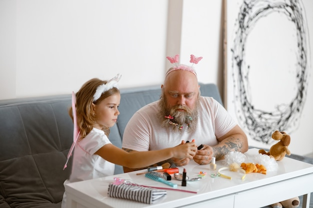 Cute little daughter with bearded daddy choose nail polish in contemporary living room