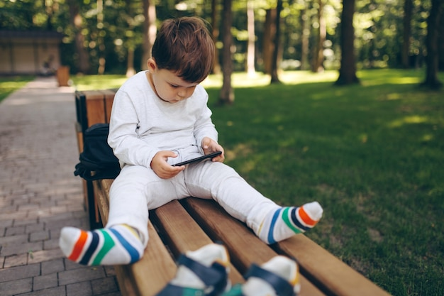 Cute little european child focused on smartphone in a bench at the park