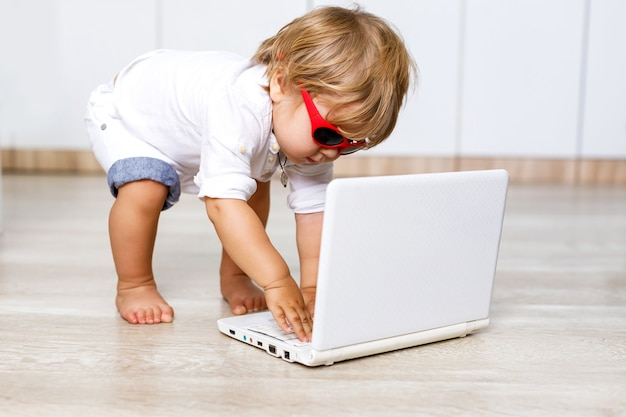 금발 머리 집에서 컴퓨터와 재미와 귀여운 작은 유럽 영리한 소년