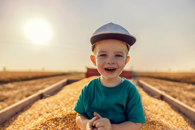 옥수수 밭에서 수확한 후 옥수수 곡물로 가득 찬 트랙터에 포즈를 취한 귀여운 농부 소년. 가을에 옥수수 수확을 돕는 귀여운 농부. 어린이와 농업
