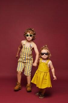 Симпатичные маленькие модные дети на розовом фоне изолировали милую девочку и кудрявого мальчика в ...