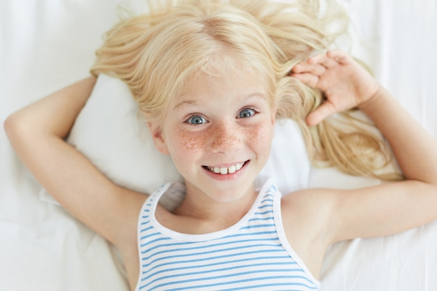 Cute little female child with blonde hair, blue eyes and freckled face, smiling joyfully while relaxing on bed, lying on white pillow.