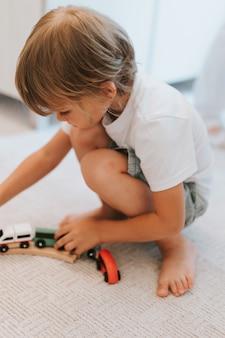 흰색 티셔츠를 입은 귀여운 다섯 살짜리 소년이 방의 카펫 바닥에서 나무 철도와 장난감 기차를 가지고 놀고 있습니다. 아이들은 집에서 놀다