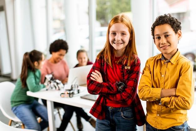 ロボット工学の教室で電気おもちゃやロボットをプログラミングする子供たちのグループの前に立っているかわいい小さな友達
